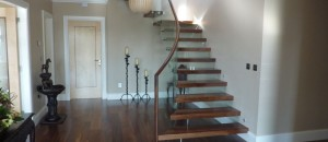 Floating glass stairs with walnut steps & handrail
